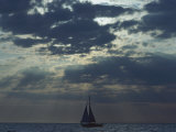 Sunlight Breaks Through a Cloudy Sky onto a Sailboat at Sea