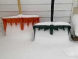 Two Snow Covered Shovels on a Porch