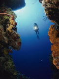 A Diver Swims Between Two Underwater Cliffs