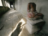 The Headless Statue of a Seated Buddha Sits in a Hallway in a Buddhist Temple