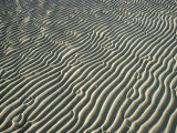 Water Forms Ripples in the Sand on a Beach