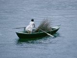 A Person Rows a Boat Full of Branches