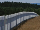 A White Picket Fence Recedes Down a Field