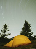 An Illuminated Tent under a Star-Streaked Sky