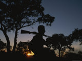 A Silhouetted Man with Rifle Enjoys Sunset at a Private Game Reserve