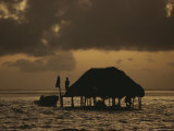 A Fishermen Watches the Sunset from His Raised Offshore Hut