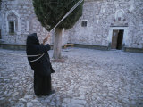 A Nun Pulls on Ropes in a Courtyard at the Nea Moni Monastery