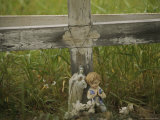 Small Statue and a Cross Draped with a Necklace Mark a Wayside Shrine