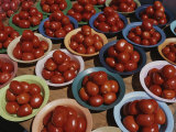 Roma Tomatoes Fill Colorful Bowls at a Vendors Stall