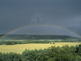 A Rainbow Spans the Sky Across a Farmers Field