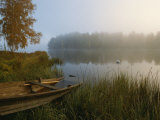 A Weathered Rowboat on the Shore of a Misty Lake