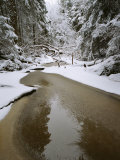 A Partially Frozen Stream Runs Through a Snowy Woodland