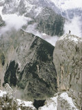 View of Snow-Covered Peaks with the Tiny Figure of a Climber Atop One