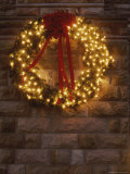 A Lighted Christmas Wreath Hangs on a Stone Building