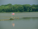 An American Flag Marks a Rock Outcrop Near a Ferry Crossing