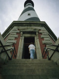 A Woman Enters the Towering Cape Hatteras Lighthouse