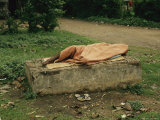 Homeless Covered Man Lies Asleep on a Slab of Cement