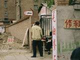Man Uses a Public Phone on a Backstreet in Beijing