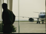 Man at a Chinese Airport Walks Past an Airplane Parked outside