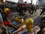 Cyclists Pass by a Street Vendor Selling Carved Pineapples