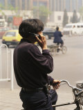 A Chinese Person Speaks on a Cell Phone While Riding a Bicycle