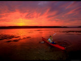 A Woman Paddles a Sea Kayak at Dusk