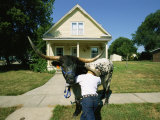 A Cowboy Struggles to Push Back His Bull on a Suburban Sidewalk