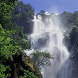 A Tall Waterfall Cascading Over Jagged Rocks