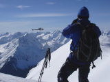 A Back-Country Skier Watches a Heli-Ski Chopper Approach a Peak