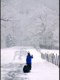 Woman Walks Along a Snowy Road with Skis and Luggage