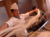 Chef Stretches Dough as He Makes Fresh Noodles in a Restaurant