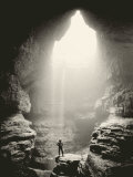 A Man Stands in Front of a Skylit Cave Waterfall