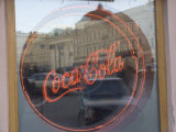 A Neon Coca Cola Sign is Displayed in a Window