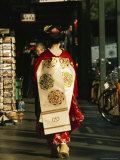 Kimono-Clad Geisha Walks Past Shops and Parked Bicycles; she is a Maiko or Apprentice Geisha
