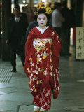 Kimono-Clad Geisha Walks Past Shops Among Other Pedestrians