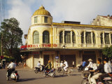 Locals Pass by an Old Colonial Building on Motorbikes in Hanoi