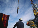 A Worker Uses a Crane and Hoist to Lift a Large Container onto an Oil Rig
