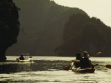Tourists Kayak Alongside Karst Limestone Formations of Halong Bay