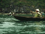 A Woman in a Traditional Boat Rows from Floating Village to Village  Halong Bay
