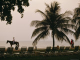 A Tourist Rides a Horse Across the Sands of a Penang Beach Resort