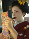 A Kimono-Clad Geisha Applies Lipstick in the Back of a Cab