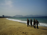 Vietnamese Soldiers Walk Along the Beach Near the Turquoise Ocean