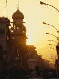 Commuters in Cars and Rickshaws Pass by a Mosque at Sunset after Work