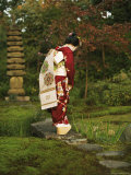Kimono-Clad Geisha Stands on a Bridge Over a Stream in a Park