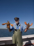 A Man Holds up Two Big Lobsters