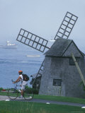 A Man on a Bicycle Passing a Windmill on the Shore in Cape Cod