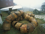 A Fishermans Baskets Piled on the Shore Near a Boat