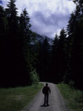 A Man Hikes Along a Road in the German Alps  Garmisch Partenkirchen  Germany