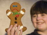 A Gingerbread Cookie Looks Sad While Being Held in a Male's Hand