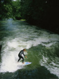 A Man Surfs on the Eisbach River in the English Garden in Munich